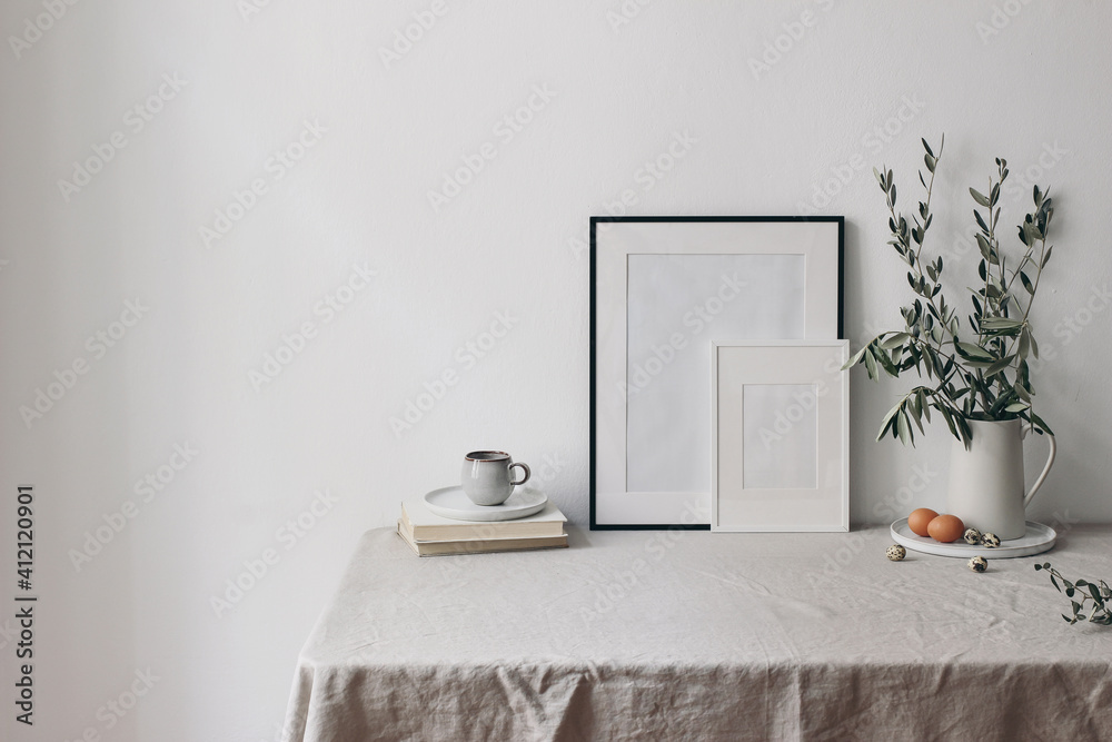 Fototapeta Spring, Easter breakfast still life. Cup of coffee, books and empty picture frames mockups. Linen tablecloth. Olive tree branches in ceramic jug. Hen, quail eggs. Farmhouse, Scandinavian interior.