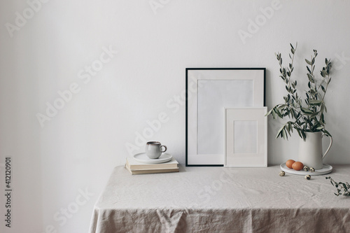Fototapeta Spring, Easter breakfast still life. Cup of coffee, books and empty picture frames mockups. Linen tablecloth. Olive tree branches in ceramic jug. Hen, quail eggs. Farmhouse, Scandinavian interior. obraz