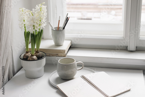 Easter spring still life. Cup of coffee, book and blank open diary mockup near window sill. White hyacinth in flower pot. Pencils in ceramic holder. Home office concept. Scandinavian interior © tabitazn