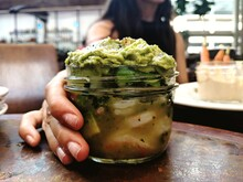 Close-up Of Hand Holding Guacamole In Jar
