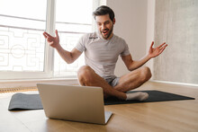 Excited Athletic Man Gesturing And Using Laptop While Working Out