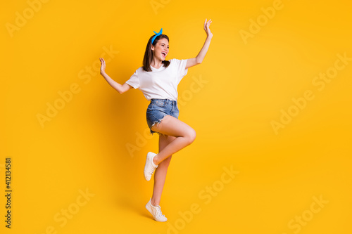 Obraz Full length body size view of slender lovely cheerful brown-haired girl jumping dancing isolated over bright yellow color background - fototapety do salonu