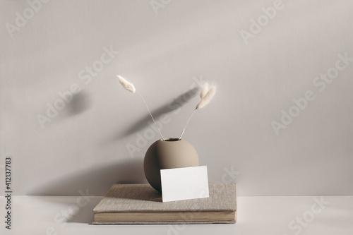 Fototapeta Modern stationery still life scene. Beige spheric vase with dry lagurus grass. Table background in sunlight. Blank business card mockups lean on old book. Champagne wall, long shadows. obraz