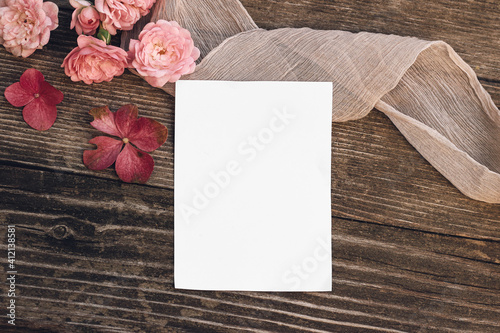 Obraz Summer wedding still life scene. Blank greeting card mock-up. Floral composition with pink roses, hydrangea flowers on old wooden table background with silk ribbon. Flat lay, top view. - fototapety do salonu