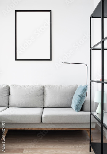 Fototapeta Blank picture frame mockup on white wall. White living room design. View of modern scandinavian style interior with sofa. Home staging and minimalism concept obraz
