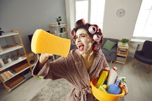 Tired Desperate Housewife Holding Yellow Sponge And Screaming Like Crazy While Cleaning House. Funny Young Woman In Hair Rollers And Beauty Skin Care Face Mask Tidying Up Home, Singing And Having Fun