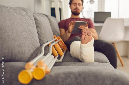 Young man with broken leg in plaster cast sitting on sofa and using tablet computer Wallpaper Mural