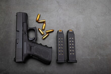 9 Mm. Semi Automatic Pistol Handgun And Ammunition Magazine On Old Cement Texture Background