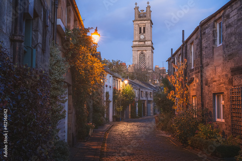 Vászonkép The picturesque and historic old town cobblestone Circus Lane and Saint Stephen's Church at night in the Stockbridge neighbourhood of Edinburgh, Scotland