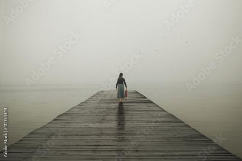 Stampa su Tela woman with suitcase walks towards her destiny