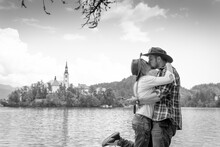 Happy Couple Of Tourists In Love Is Kissing On The Background With Bled Lake And Church On The Island, Slovenia. Summer Time In Europe. Copy Space. Black And White
