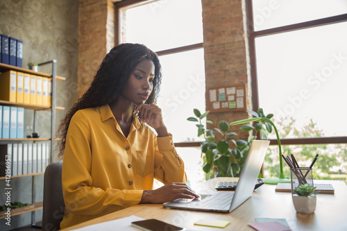 Profile side photo of afro american woman work office laptop serious executive in workspace indoors in office