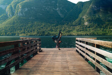 "Man Froze In A Dance Stand Alone On A Wooden Pier At A Mountains Over Water. Summer Sunset Time. Travel And Freedom Concept ""Bohinjsko Jezero"" Slovenia"