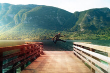 """Man Happy Jump Alone Standing On A Wooden Pier At A Mountains Over Water. Summer Sunset Time. Travel And Freedom Concept """"Bohinjsko Jezero"""" Slovenia"""