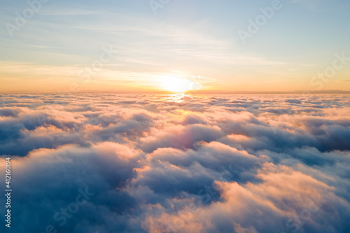 Fototapeta Aerial view of bright yellow sunset over white dense clouds with blue sky overhead. obraz