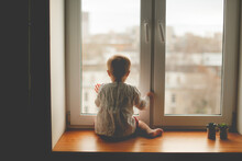 Cute Caucasian Infant Toddler Child Sitting On The Window With His Back, Baby Safety And Waiting, Lifestyle And Toning