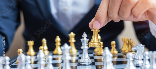 Cuadros en Lienzo businessman hand moving gold Chess King figure and Checkmate opponent during chessboard competition