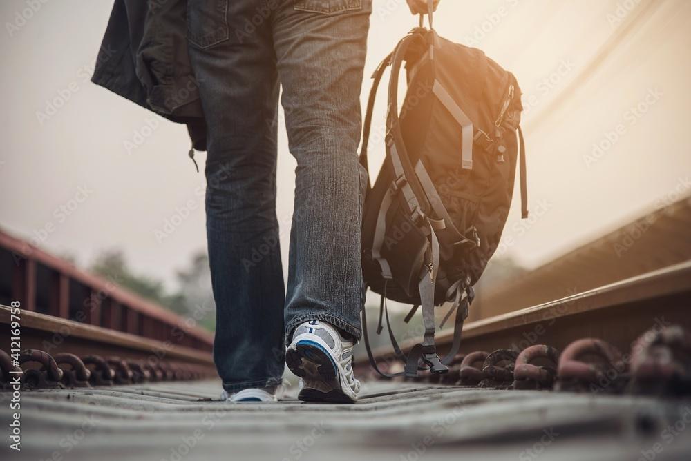 Fototapeta Low Section Of Man Walking On Railroad Track