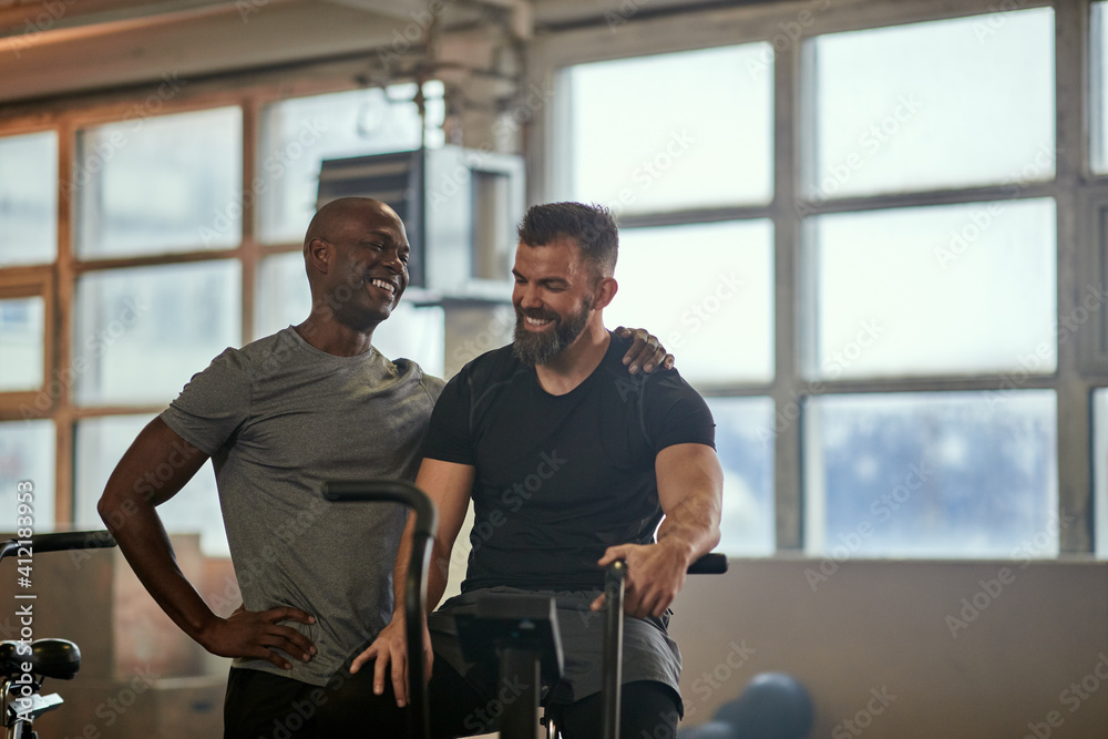 Fototapeta Two men laughing after a stationary bike exercise session