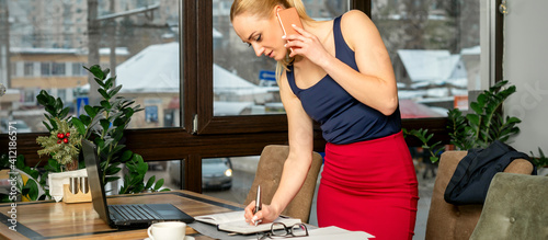 Young businesswoman talks on the phone writing notes standing in office or cafe