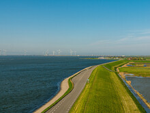 Sea Dike With Wind Turbines And A Marina In Zeeland, The Netherlands