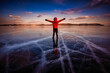 Leinwandbild Motiv Traveler man wear red clothes and raising arm standing on natural breaking ice in frozen water at Lake Baikal, Siberia, Russia.