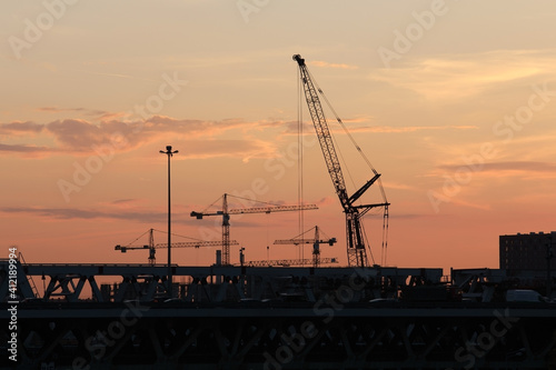 Construction cranes at work at sunset © Alexey Kuznetsov