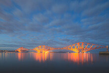 Night View Of The 19th Century And Unesco Heritage Site Forth Rail Bridge Over The Firth Of Forth At The Queensferry Crossing North Of Edinburgh, Scotland.