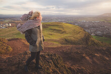 A Young Blonde Female Tourist With A Scarf Looks Out To A Cityscape View Of Edinburgh, Scotland On A Windy Afternoon Up Arthur's Seat.