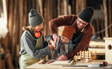 Happy family doing woodwork together in workshop