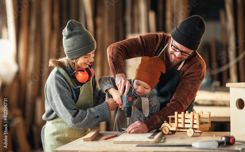 Happy family doing woodwork together in workshop Wallpaper Mural