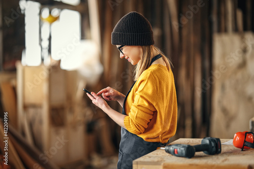 Female joiner using smartphone in workshop