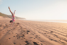 A Young Blonde Female Tourist Does A Cartwheel On The Sand At Tafedna Beach In The Province Of Essouira, Morocco.