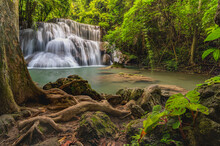 Beautiful Waterfall In The Middle Of The Forest With Rocks And Roots In The Foreground,Kanchanaburi,Thailand