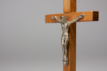 Horizontal Close-up Conceptual Photography Of A Crucifix With A Silver Figurine Of Jesus Christ On The Wooden Cross, Against Light Grey Background