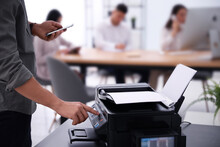 Employee Using Modern Printer In Office, Closeup