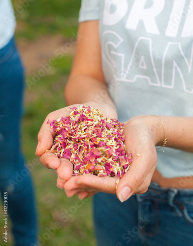 Heart shape hands of girl holding dry flowers petals to blow at a party.
