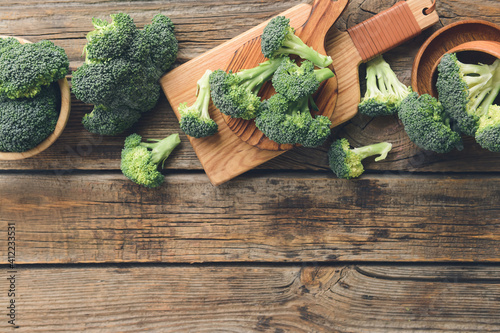 Photo Board with fresh broccoli cabbage on wooden background
