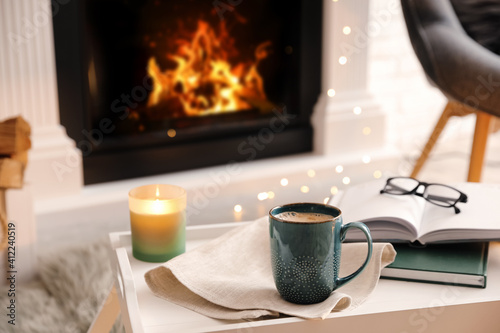Fototapeta Cup of coffee, burning candle and books on tray near fireplace indoors. Cozy atmosphere obraz