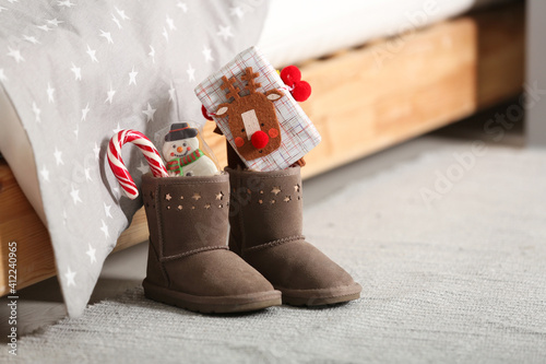 Canvas Print Sweets and gift box in child's boots near bed indoors