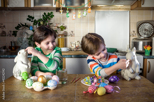 Two little kid boy coloring eggs for Easter holiday in domestic kitchen, indoors Fototapeta