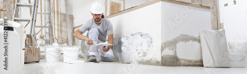 plasterer man at work, take the mortar from the bucket with trowel to plastering the wall of interior construction house site and wear helmet, panoramic image