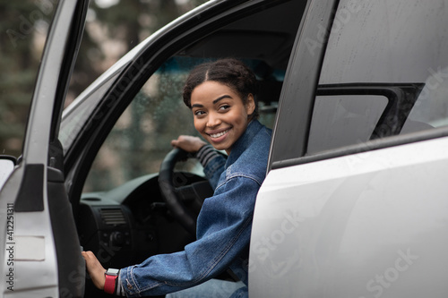 Fototapeta Friendly smiling millennial african american female driver opens door and looks for fellow traveler obraz
