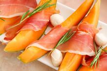 Plate With Delicious Melon, Mozzarella And Prosciutto On Color Background, Closeup