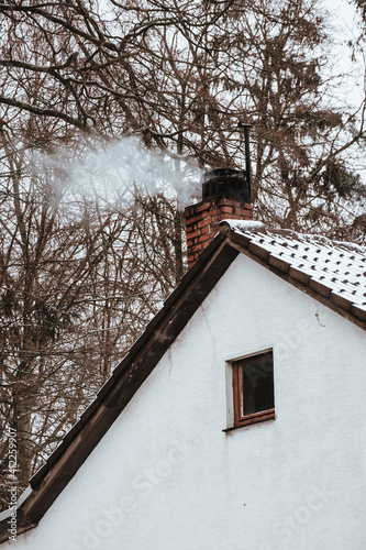 Photo Vertical shot of smoke coming out of a chimney on the snow-covered rood of a hou