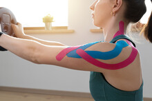 Young Fit Women Performing Excersise With Elastic Therapeutic Kinetic Tape On Her Shoulder On A Sunny Day At Home. Kinesiology Physical Therapy.