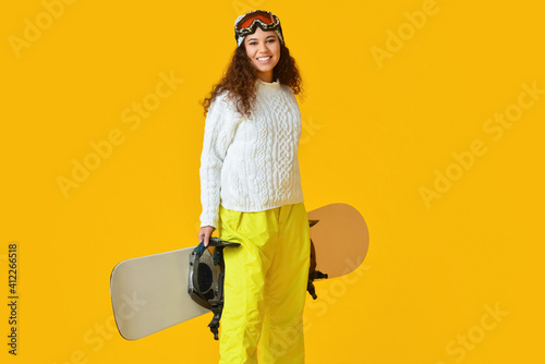 Photo Female snowboarder on color background