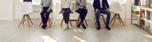 People Are Waiting In The Waiting Room. Cropped Image Of The Legs Of Various People Sitting On Chairs And Waiting Their Turn For An Interview. Concept Of Employment, Clients And Human Resources.
