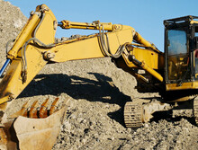 Excavator At Work: The Mechanical Shovel Of A Bulldozer In An Excavation Site.