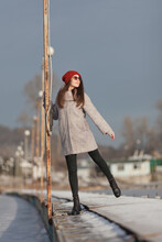 A Girl In A Gray Coat And A Red Hat Poses Near A Lamppost On The Pier In Sunglasses. Winter. Coldly. Ice. Sunny.